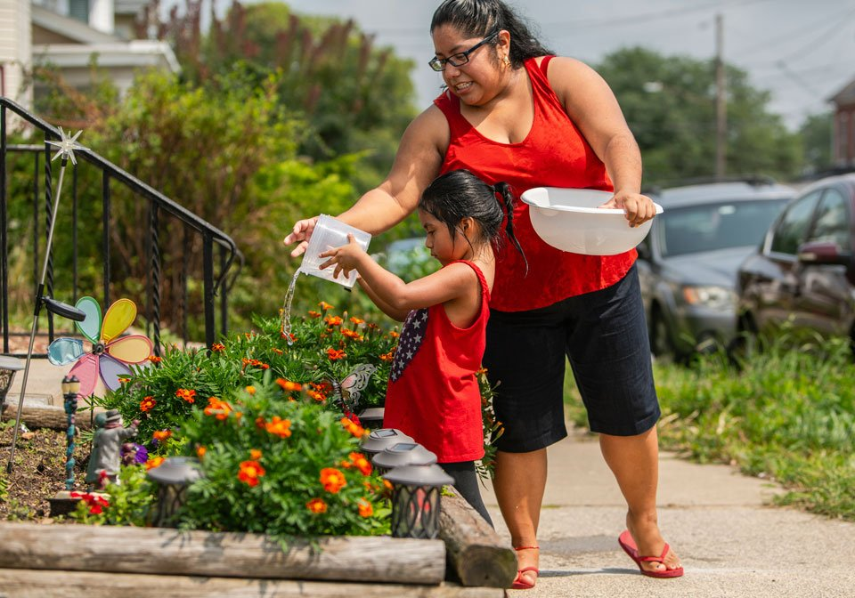 mother and daughter watering flowers