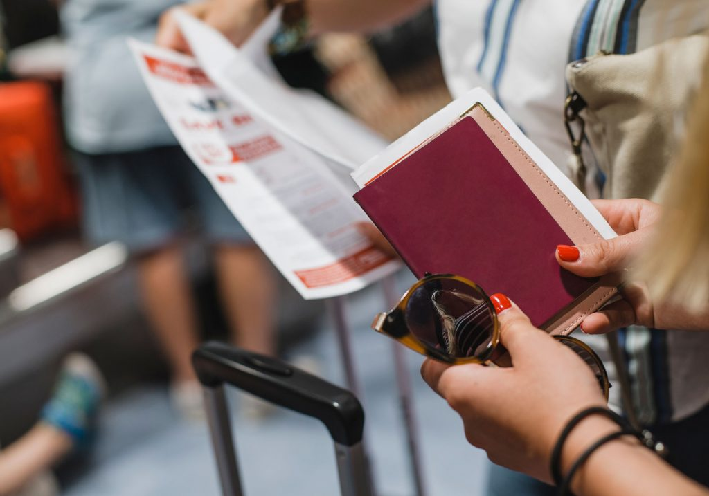 Female hands holding red passport while waiting in line at airport