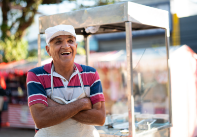 Man smiling and standing next to his food cart