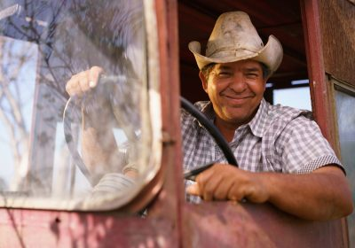 Older Latin American man wearing a rancher hat and driving a pickup truck