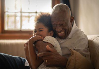 Grandfather tickling granddaughter