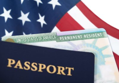 United States passport and green card sitting on American flag