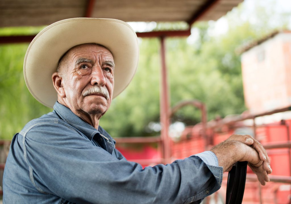 Older farmer resting on his tractor