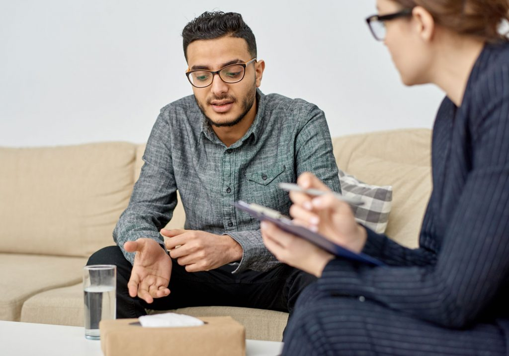 Man sitting on couch, talking to therapist